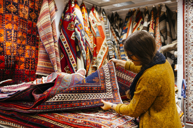 Woman browsing through selection of rugs in home goods store