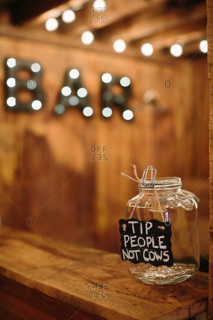 Humorous tip jar on a bar at a wedding