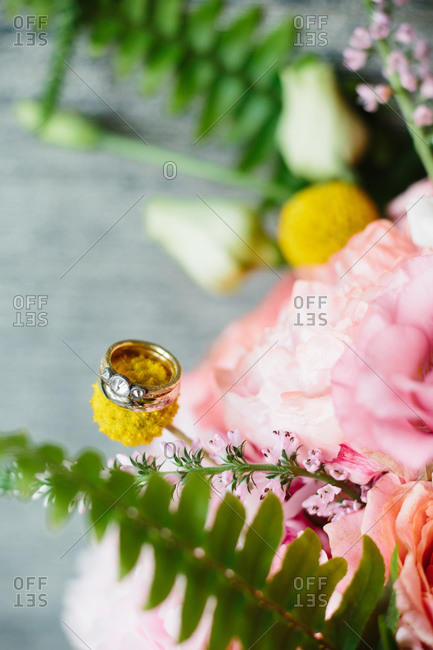 Wedding and engagement rings displayed on bride's bouquet