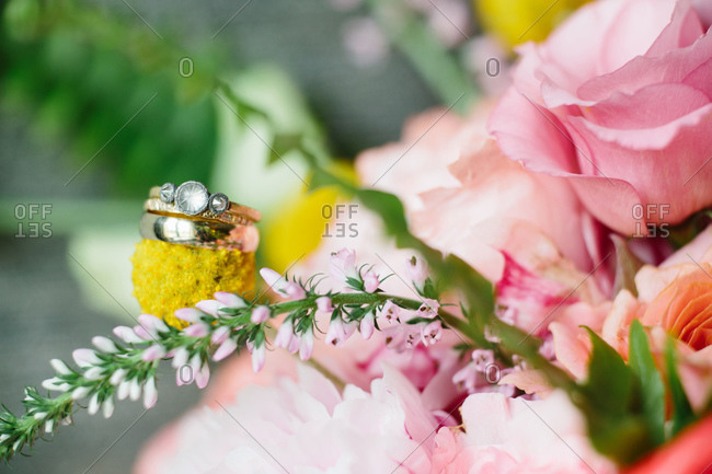 Engagement and wedding rings displayed on bride\'s bouquet