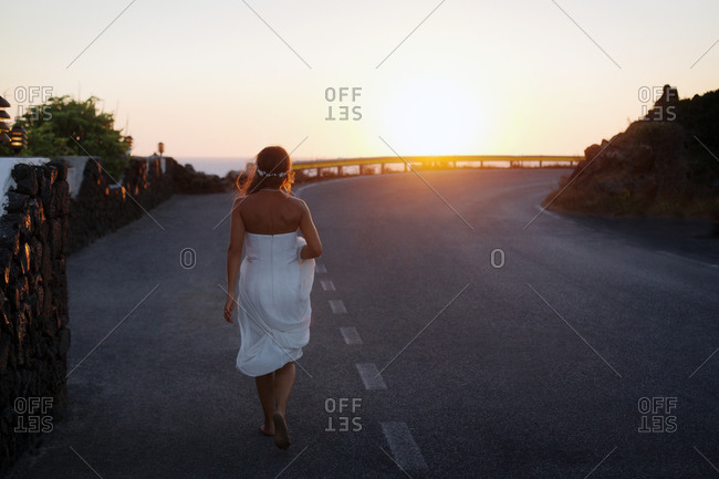 Bride walking along a road at sunset