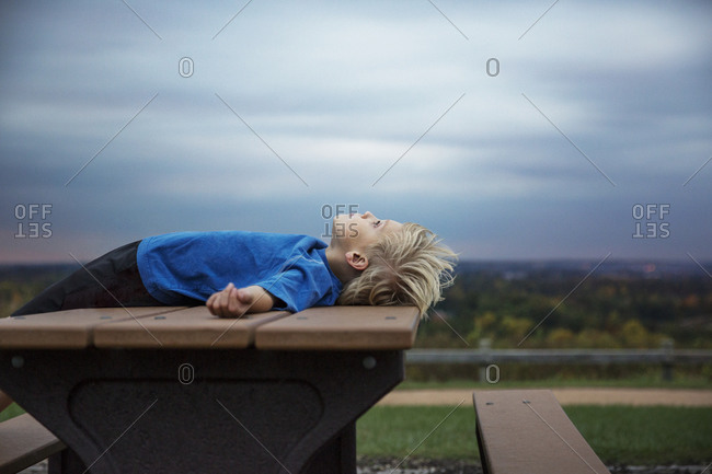 Boy lying on picnic table looking up at sky