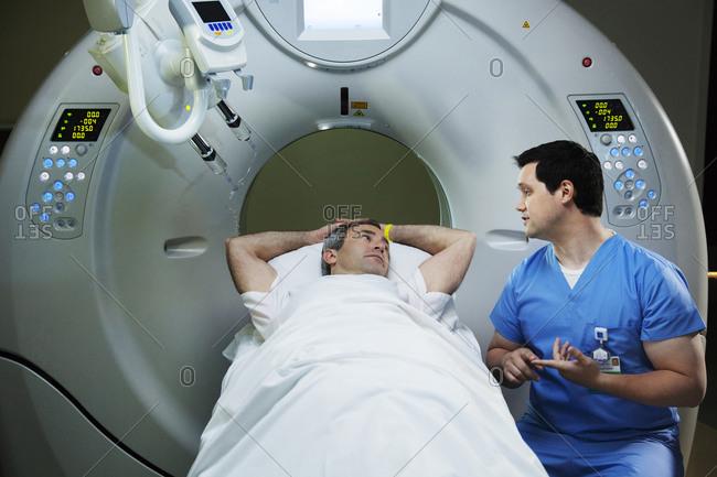 Technician explaining CT scan procedure to patient
