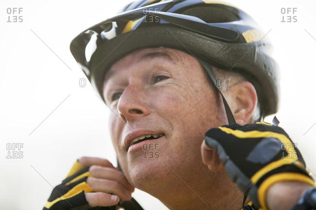 Senior man buckling bike helmet straps