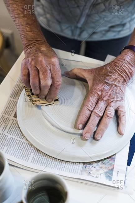 Ceramist finishing a handmade plate
