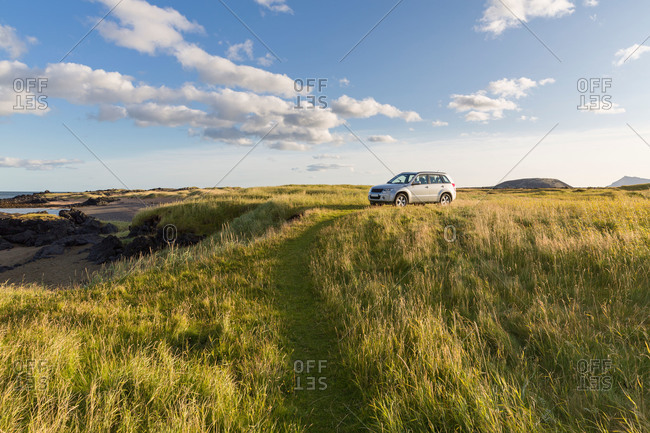 Four-wheeled drive vehicle parked in grassy field on Iceland coast