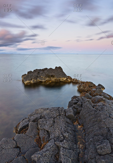 Rock outcropping in sea at sunset, Iceland