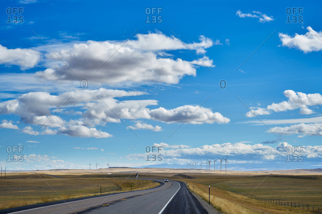 Highway through open fields with wind turbines