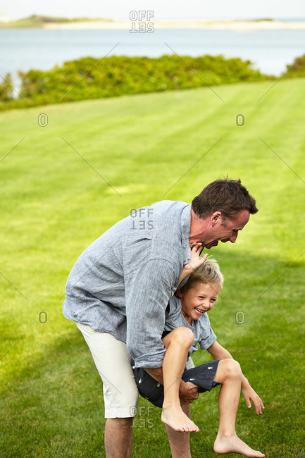 Bridgehampton, NY, USA - August 3, 2013: Chef Marc Murphy playing with his son on green lawn in coastal backyard