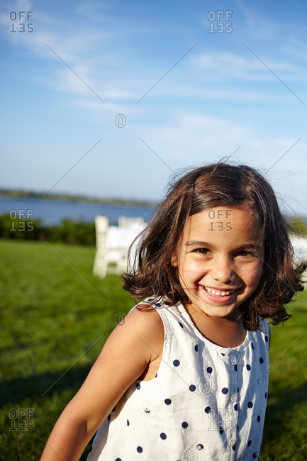 Bridgehampton, NY, USA - August 3, 2013: Portrait of a happy young girl standing in coastal backyard