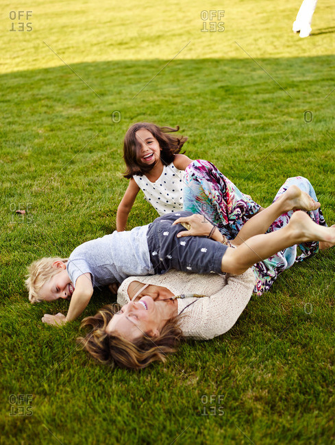 Bridgehampton, NY, USA - August 3, 2013: Two children rolling on lawn with their mother