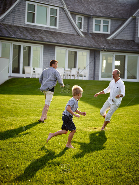 Bridgehampton, NY, USA - August 3, 2013: Two men running around lawn with boy in Hamptons backyard
