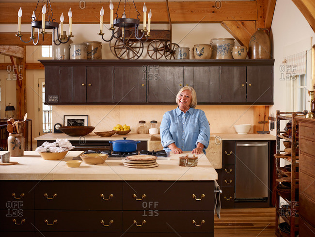 Hudson Valley, NY, USA - February 17, 2014: Portrait of woman at countertop in a farmhouse-style luxurious kitchen