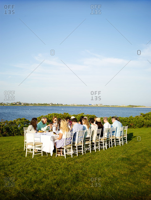 Bridgehampton, NY, USA - August 3, 2013: Large group of family and friends dine at long table set on waterfront lawn in the Hamptons