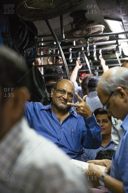 Mumbai, India - January 20, 2015: Man making gesture on crowded Mumbai train