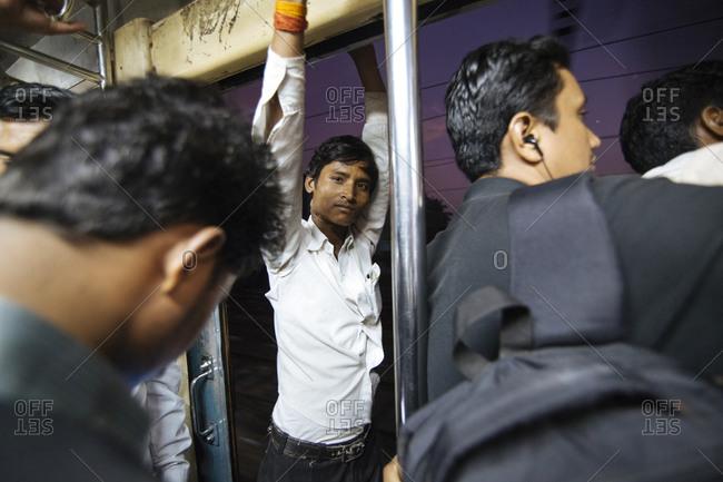 Mumbai, India - February 7, 2015: Man in doorway of crowded Mumbai train