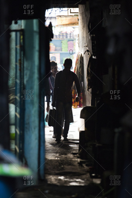 Mumbai, India - February 7, 2015: Man carrying suitcase in Mumbai alley
