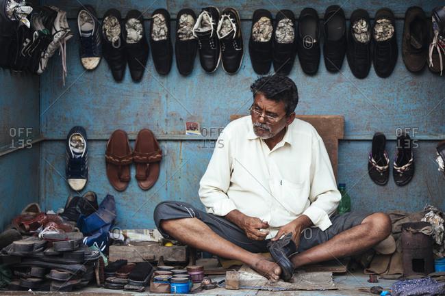 Mumbai, India - February 7, 2015: Man sewing shoes in Mumbai street