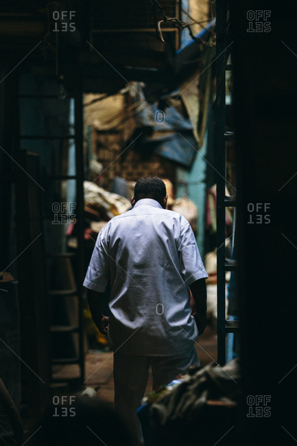Man walking in alley of Mumbai slum