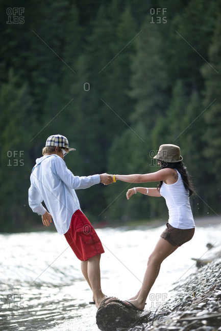 A girl and boy hold onto each other for balance on a log on the shore of Lake Pend Orielle, Idaho