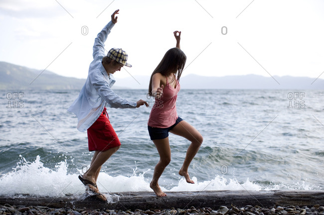Two friends try to balance as they walk across a log on the shore of a lake in Idaho