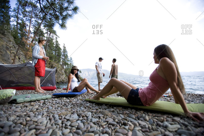 Girls relax on their sleeping bags while camping with their friends along the shore of Lake Pend Oriellie, Idaho