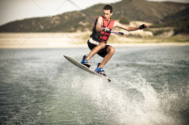 A teenage boy jumps the wake on his wakeboard