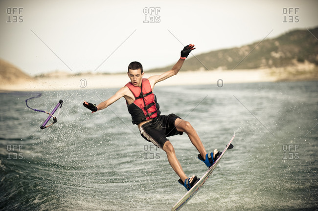 A teenage boy in the middle of the air and falling on his wakeboard