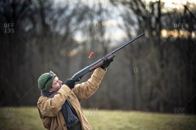 A man shoots a shotgun at a clay target from a skeet machine