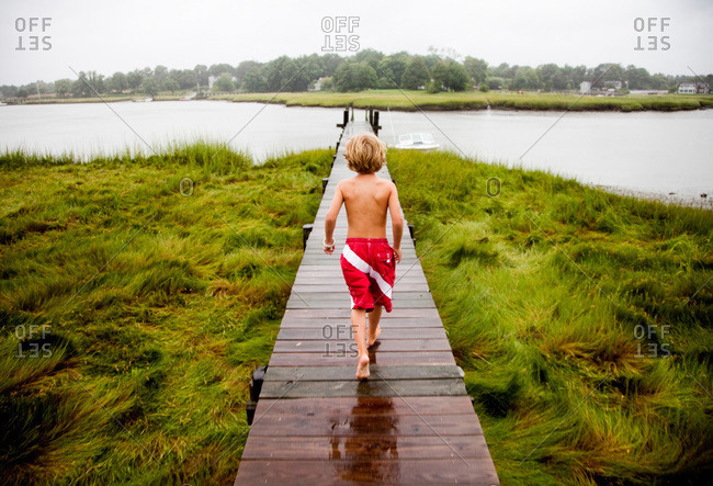 A young boy walks on a raised boardwalk over lush marsh grasses after swimming in a small inlet
