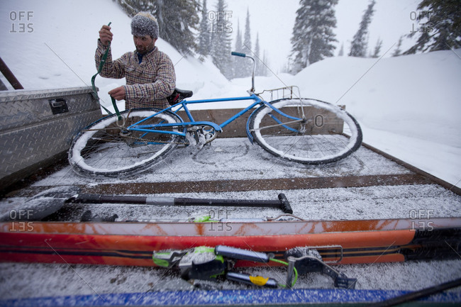 A man tying a bike into the back of a truck in winter