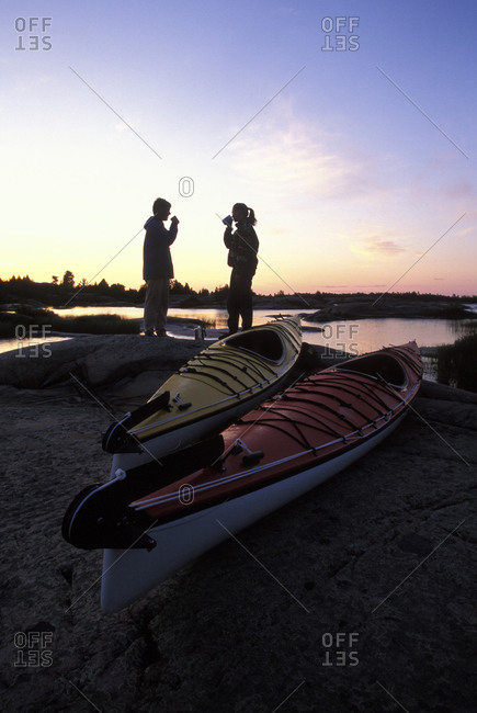 Young couple camped on shore of Georgian Bay with sea kayaks, Lake Huron, Ontario, Canada