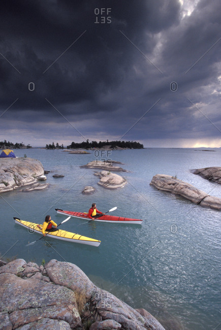 Young couple sea-kayak near storm on Georgian Bay, Lake Huron, Ontario, Canada