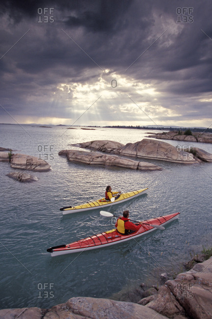 Young couple sea-kayak after a storm on Georgian Bay, Lake Huron, Ontario, Canada