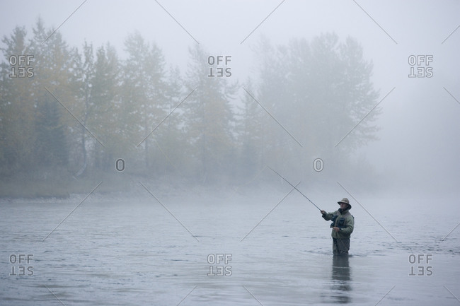 A man fly-fishing on Elk River, BC, Canada on a foggy day