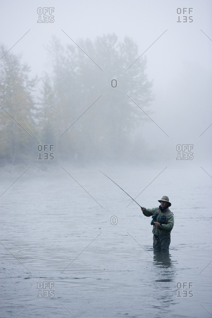 A man fly-fishing on Elk River, BC, Canada on a misty day