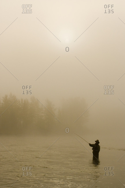 A man fly-fishing on Elk River, BC, Canada on a hazy morning