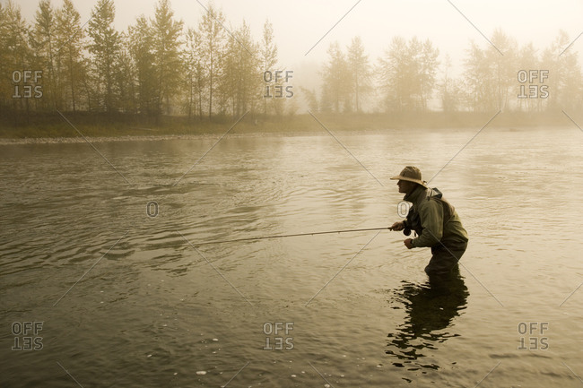 A man fly-fishing on Elk River, BC, Canada on a misty morning