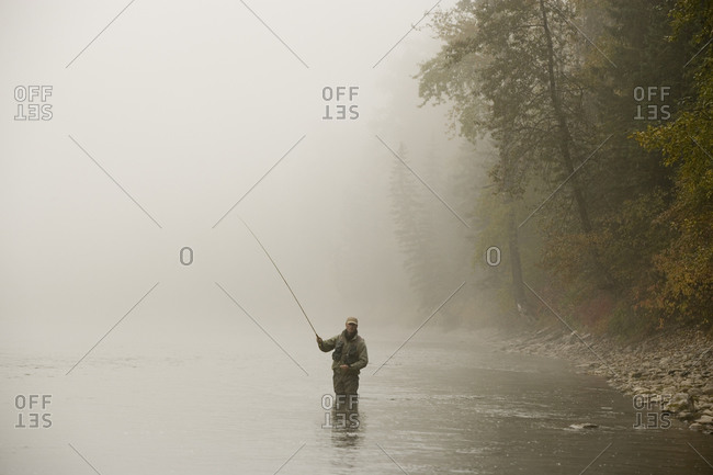 Middle-aged man fly-fishing on Elk River, British Columbia, Canada