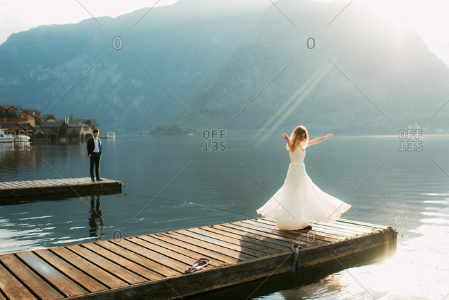 Groom watching his bride twirl her dress on a wooden pier