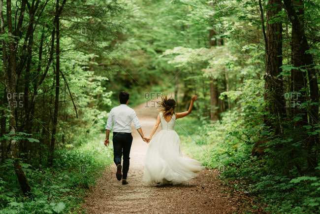 Bride and groom running through a path in the forest