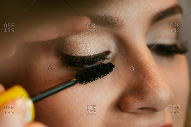 A young bride having mascara put on
