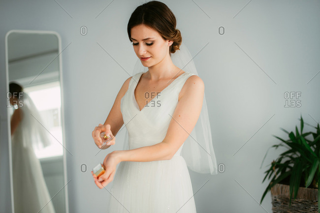 A young bride putting perfume on her wrists