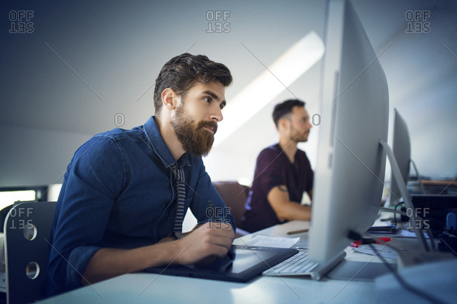 Bearded man using a tablet and stylus at his computer