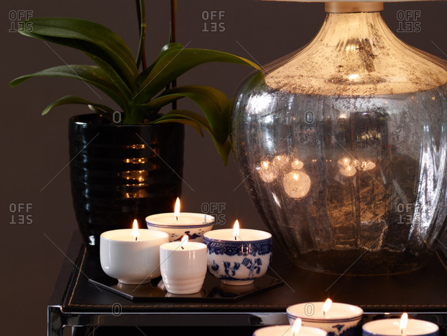 Candles arranged on a side table with lamp and plant
