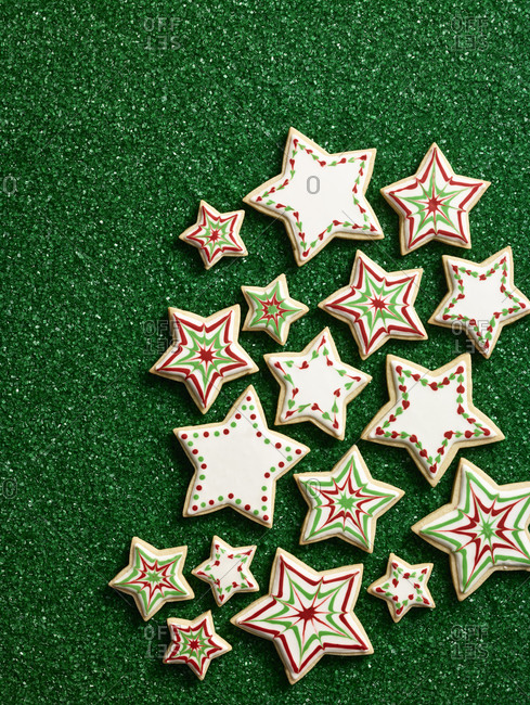 Group of star shaped sugar cookies on a green background