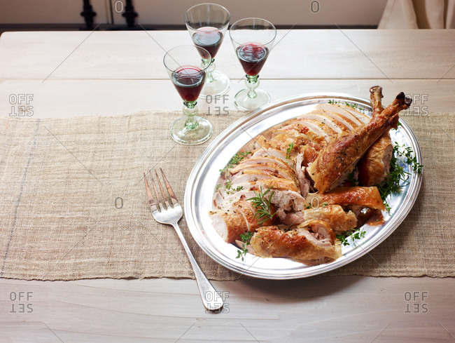 Serving platter with sliced turkey and glasses of red wine