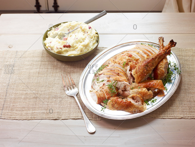 Serving platter with sliced turkey and mashed potatoes