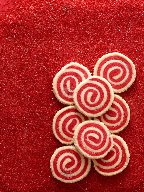 Red swirl sugar cookies on a red glittery background