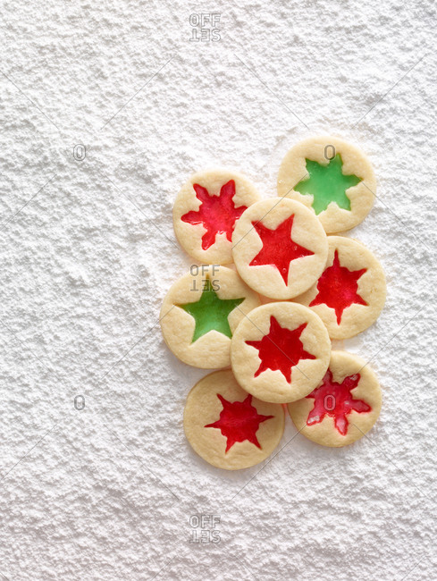 Jam filled sugar cookies on a white sugary background